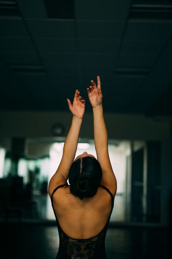 Rear view of woman with hands raised at dance studio