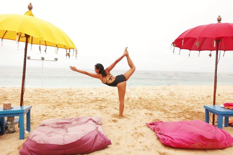 Woman doing yoga on beach against sky