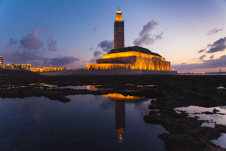 View of hassan ii mosque reflected on sea water at sunset - casablanca - morocco