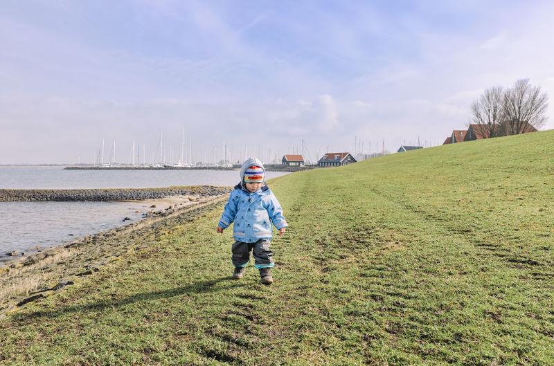 Full Length Of Boy Walking On Field Against Sky