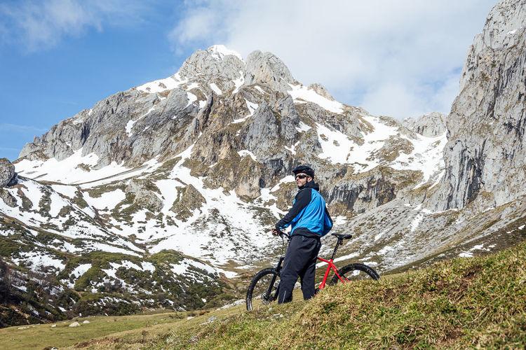 Full length of man on snowcapped mountain against sky