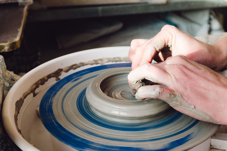 Midsection Of Person Working Pottery Wheel