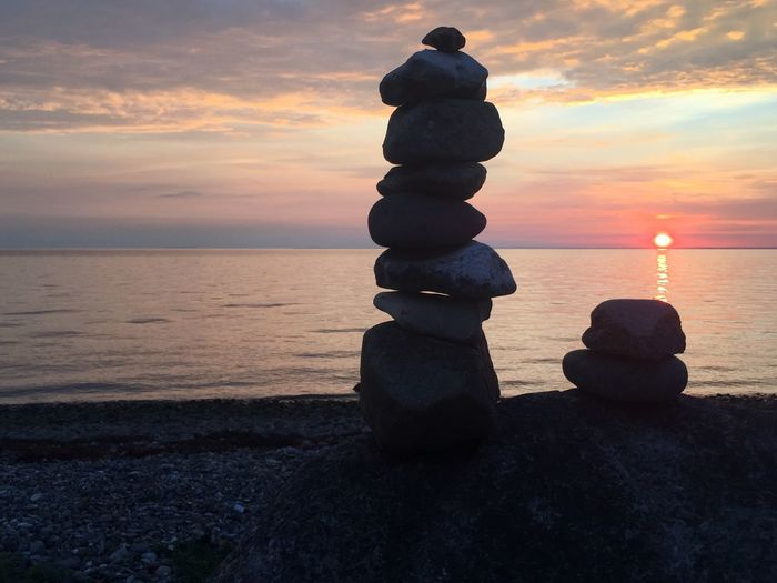 Stack of pebbles on beach against sky during sunset
