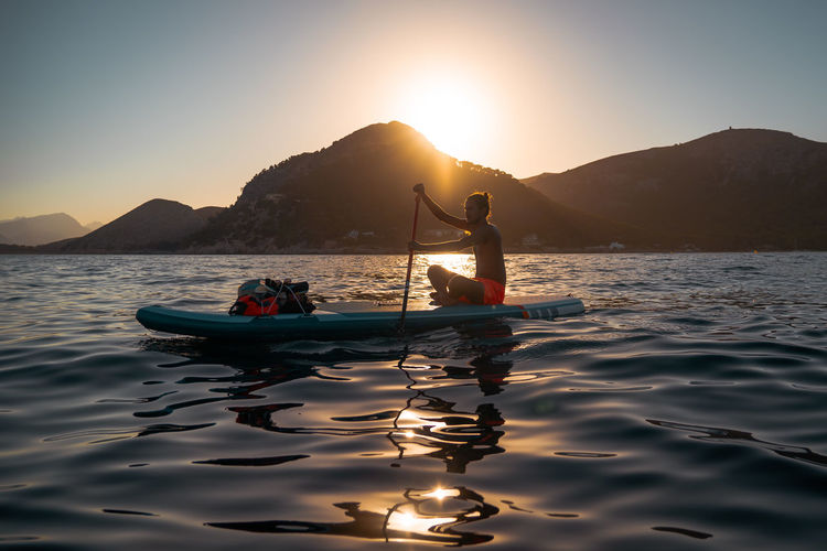 Man with paddle board over golden hour landscape
