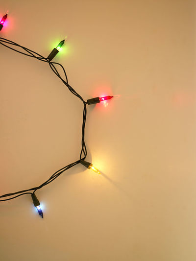 Close-Up Of Illuminated String Light Over Yellow Background