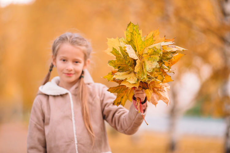 Portrait of smiling girl holding leaves during autumn