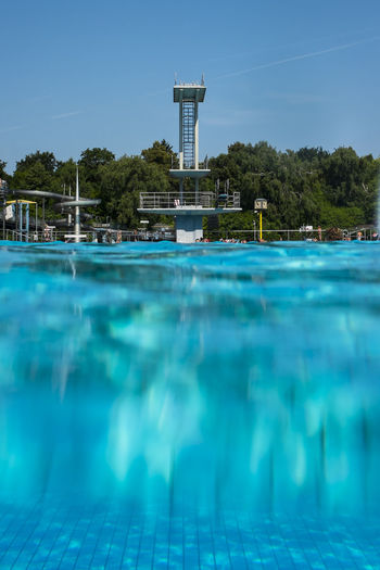 Outdoor pool with blue water and tower in the background