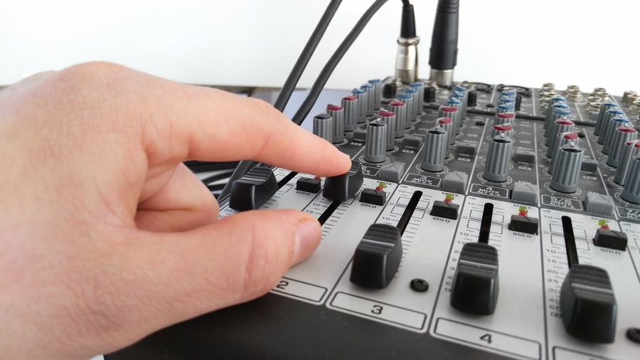 Cropped Hand Of Person Adjusting Audio Equipment Against White Background