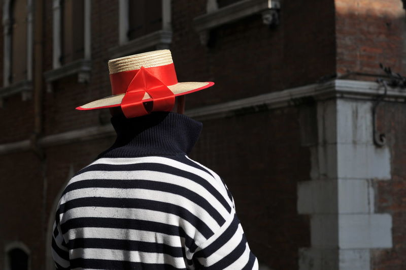 Gondolier operator looking over a canal. Standing Focus On Foreground Leisure Activity Lifestyles Celebration Hat Adult Venice Gondolier Operator Gondolier Costume Uniform Red Ribbon Striped Jumper Boater Hat Straw Hat Woven Straw Giuliana's Hat Cultural Heritage Cultures Red