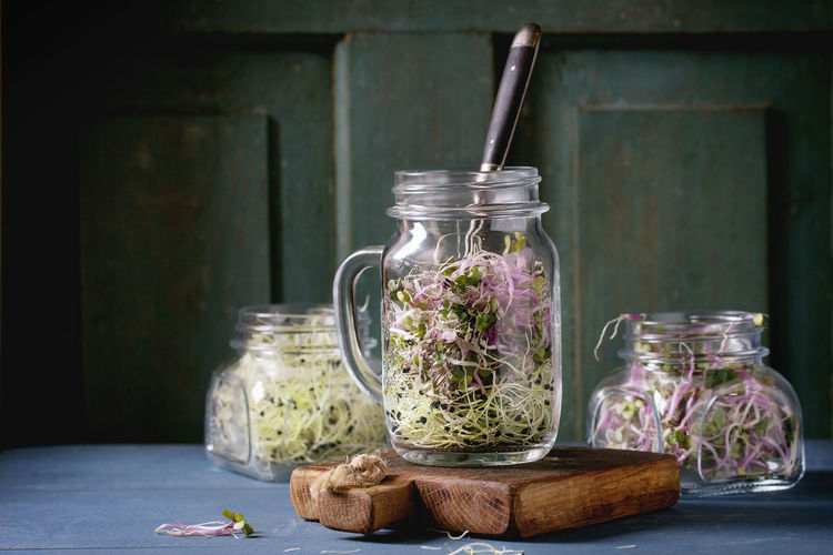 Close-up of bean sprouts in jars on table against door