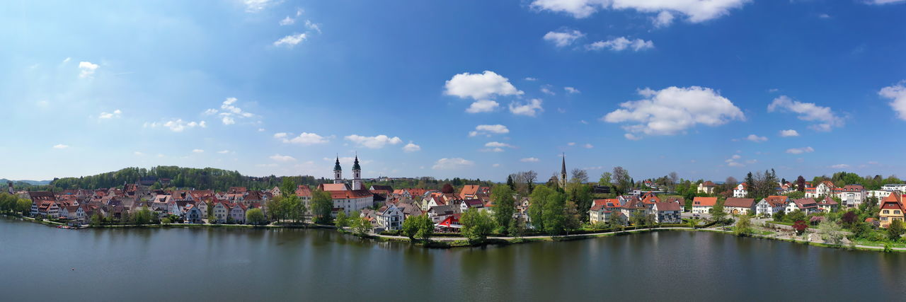 Panoramic shot of townscape by canal against sky