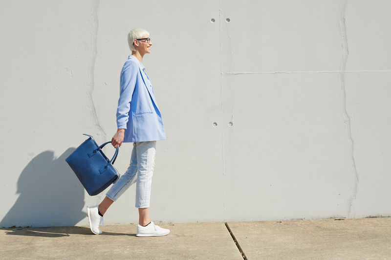 Woman with bag walking by wall