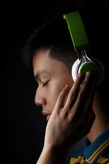 Teen listening to music on a headphone. One Person Holding People Young Adult Young Youth Youth Of Today Millenials Kid Teenager Boy Male Music Musician Musical Equipment Headphones Earphones Technology Electronics  Sound Volume Tone Headshot Close-up Human Body Part