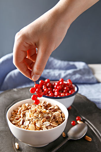 Cropped image of hand holding red current over oatmeal on table
