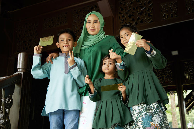 Kids happy after receiving green packet as pocket money from mother