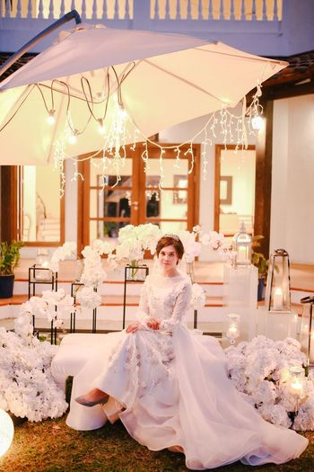 Full Length Portrait Of Bride Wearing Wedding Dress Sitting Against House At Night