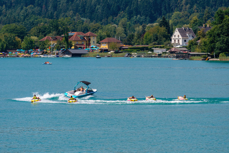 WORTHERSEE, AUSTRIA - AUGUST 08, 2018: Happy young people, on inflatable attractions, drive behind a motorboat on the lake. Nature Day Outdoors Austria Carinthia Carinthian Lakes Tourist Tourists Lake Wörthersee Recreation  Leisure Landscape Water Sea Boats Motorboat Speedboats Summer People Holidays Fun Travel Beach Resort Lifestyle Sunny Rest Joy Waves Europe Alps Alpine Alpine Lake Nautical Vessel Waterfront Transportation Built Structure Mode Of Transportation Architecture Mountain Real People Tree Building Exterior Men Group Of People Lifestyles