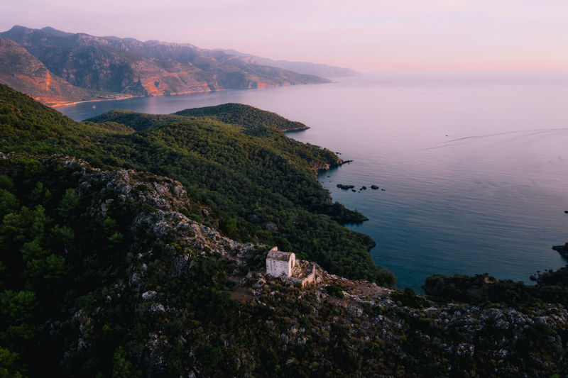 Sunset over a lone church perched high above the ocean in Turkey Kayakoy Turkey Abandoned Aerial View Dramatic Sky Drone  Dronephotography Sunset Travel Destinations Fetiyeh Built Structure Ocean Check This Out Wanderlust Week On Eyeem Water Beauty In Nature Non-urban Scene Outdoors Mountain Tranquility Scenics - Nature Sky Nature Sea