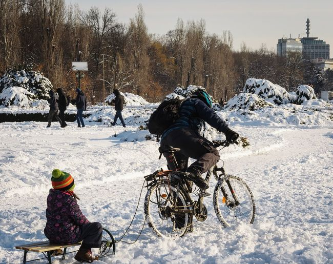 People riding motorcycle on snow during winter