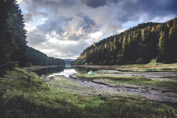 Wilderness tent camping against blue cloudy sky on sunrise Camping Cloudy Beauty In Nature Cloud - Sky Environment Flowing Flowing Water Forest Lake Land Landscape Mountain Nature No People Non-urban Scene Plant Scenics - Nature Sky Sunrise Tent Tranquil Scene Tranquility Tree Water Wilderness
