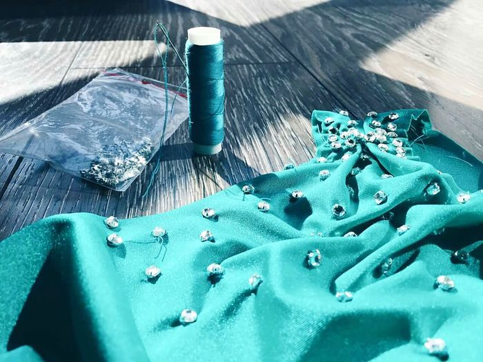 Diamonds on turquoise fabric by spool on wooden table