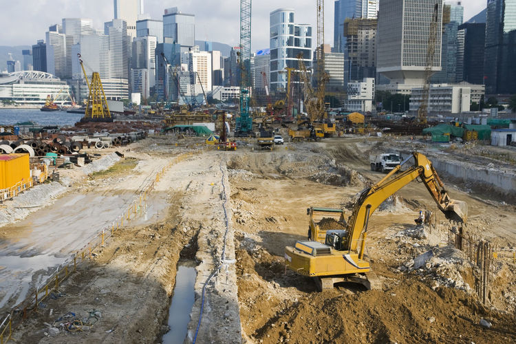 Panoramic shot of construction site by buildings in city