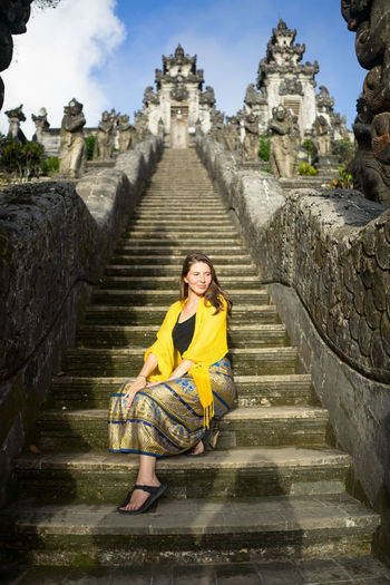 Adult Ancient Architecture Built Structure Casual Clothing Front View Full Length History Nature One Person Outdoors Portrait Sitting Staircase Steps And Staircases The Past Tourism Travel Destinations Women Yellow Young Adult