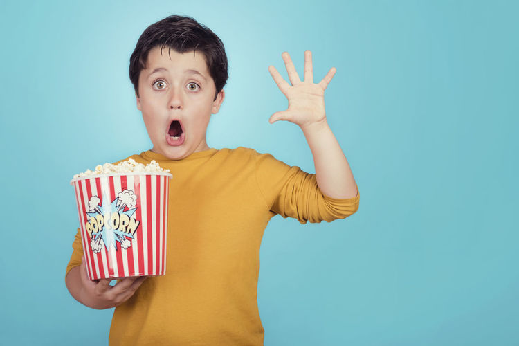 Expressive Film Fun Funny Happy Hungry Lifestyle Popcorn Snack Appetite Blue Background Child Childhood Cinema Eat Emotion Expression Leisure Movıe People Portrait Surprise Television Waist Up