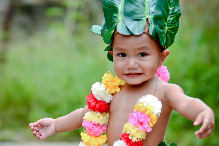 Portrait of cute boy wearing leaves and garland standing outdoors