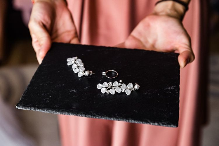 Midsection of woman holding jewelry on slate