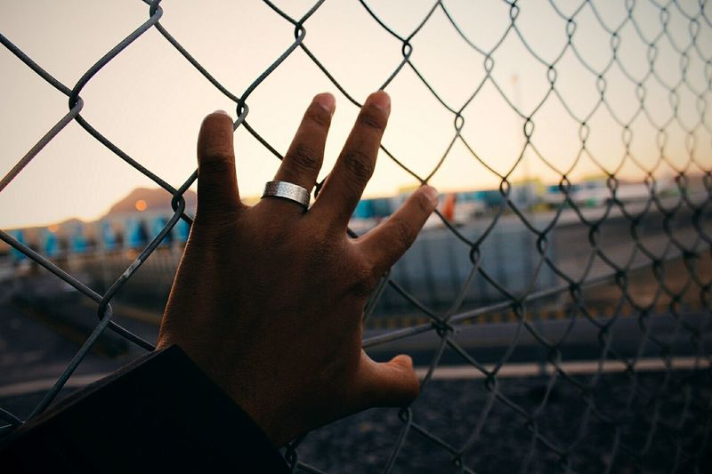 Cropped hand of man touching chainlink fence