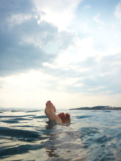 Low Section Of Woman Swimming In Sea Against Cloudy Sky