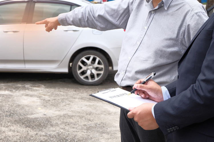 Midsection of salesman discussing with customer while standing by car