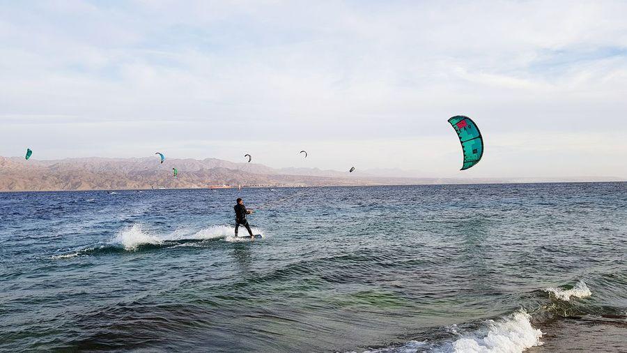 Man windsurfing in sea against sky