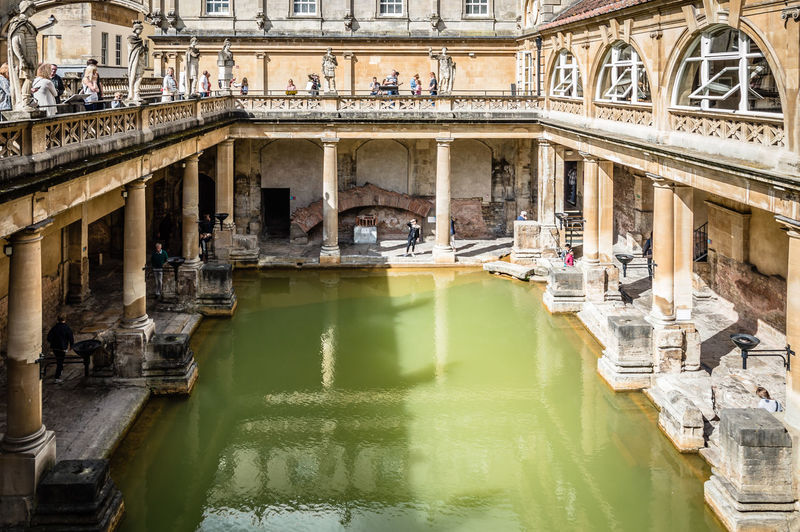 The Roman Baths in Bath Ancient Arch Architecture Bath Building Building Exterior Built Structure Canal City City Life Day Hot Spring Outdoors Reflection Residential Building Roman Ruins Standing Water Tourism Travel Destinations Water Water Reflections