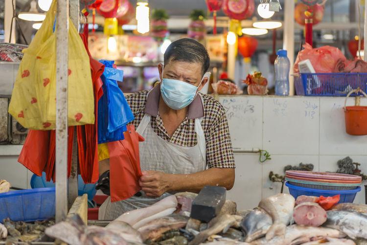 Woman having food at market stall
