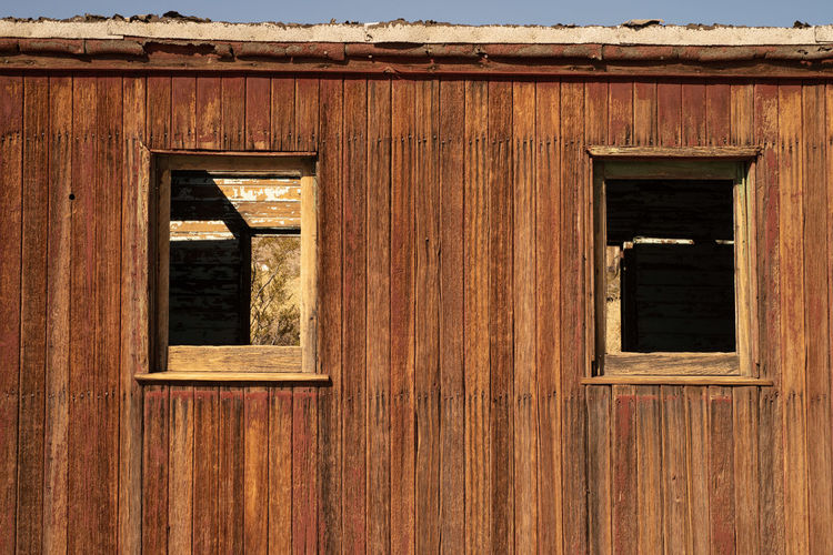 windows in the side wood wall of abandoned railroad caboose in ghost town of Rhyolite, Nevada, USA Train Car Abandoned Brown Built Structure Caboose Closed Day Deteriorated Door Entrance Full Frame Geometric Shape Ghost Town Nevada No People Old Outdoors Railroad Car Rhyolite Security Window Window Frame Windows Wood Wood - Material