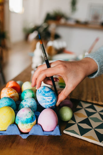 Midsection of person holding colorful easter eggs on table