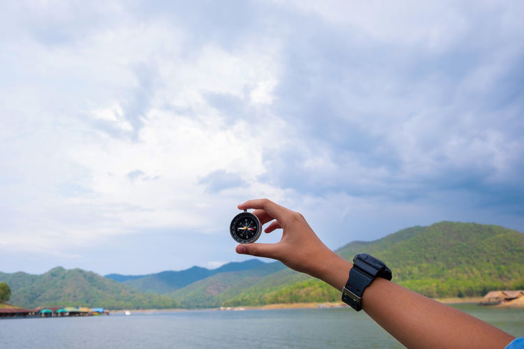 Cropped hand holding navigational compass by lake
