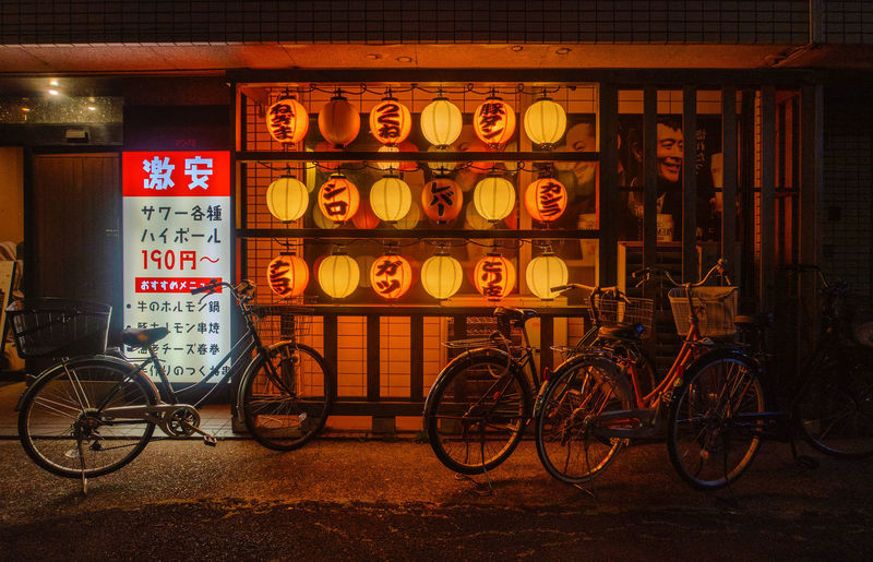 Bicycle parked on illuminated sign at night