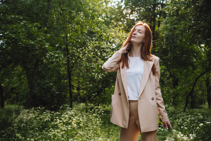Young woman standing by plants in forest