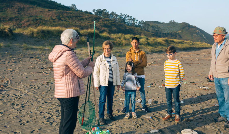 Family looking at senior woman while holding fishing net at beach