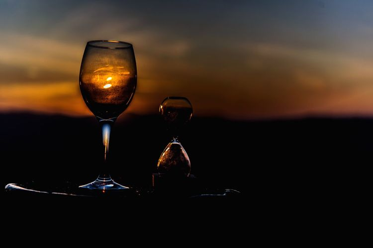 Close-up of wineglass and hourglass against sky during sunset