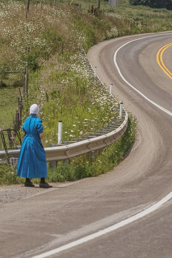 Rear View Of A Woman Walking On Country Road