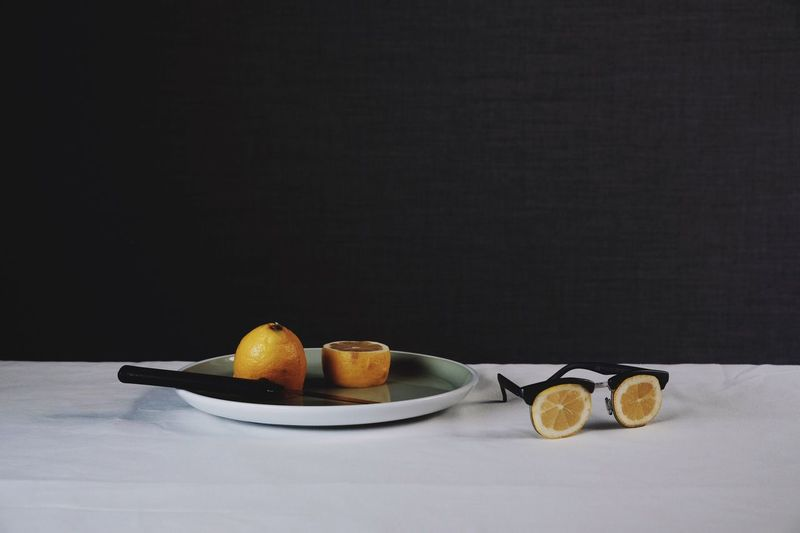 Close-Up Of Fruits In Plate On Table Against Black Background