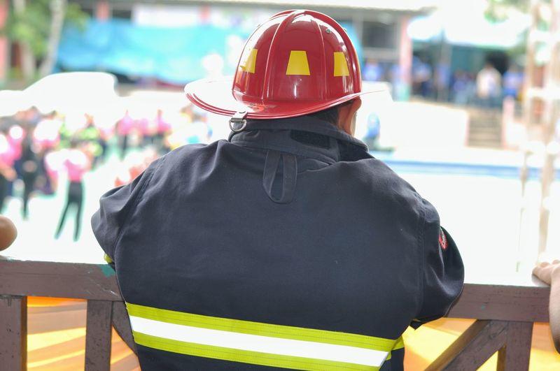Rear view of firefighter wearing uniform