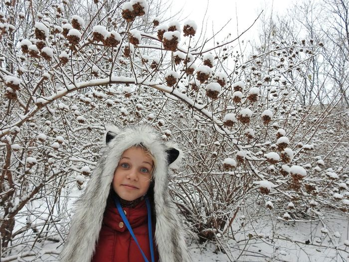 Close-up portrait of girl standing against snowcapped trees