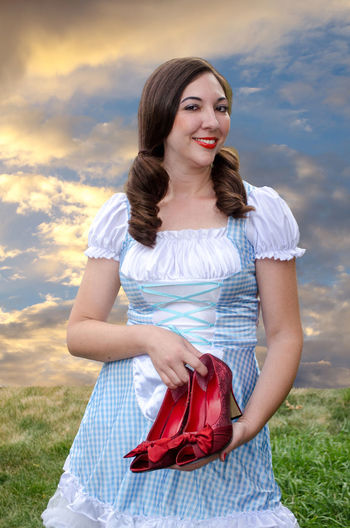 Portrait Of Woman In Traditional Clothing Holding High Heels Against Cloudy Sky
