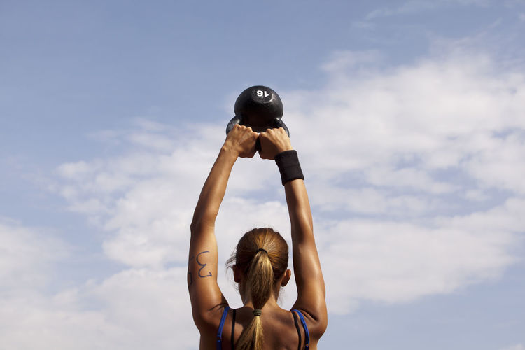 Crossfit. Young woman doing kettlebell swings at sports competition. Athlete Back Bell Kettle Lifting Swinging Wellness Woman Working Arm Cloud - Sky Competition Crossfit Exercising Female Fitness Kettlebell  Lifestyles Muscles One Person Outdoors Sky Sport Strength Training