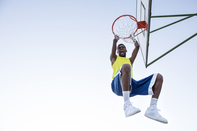 From below shot of black man in sportswear hanging on hoop and shouting happily. Adult Basketball Confidence  Determination Ethnicity Expressive Hanging Hoop Man Motivation Sportsman Action Basket Black Blue Sky Ethnic Excitement Expression Furious Muscular Passion Player Screaming Sportsground Streetball